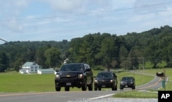 FILE - Official vehicles drive down a road near Camp David, Maryland, Aug. 18, 2017.