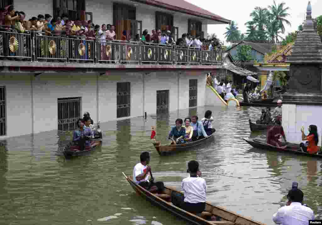 Myanmar opposition leader Aung San Suu Kyi (center) leaves a monastery by boat after visiting flood victims sheltered in Bago, 80 kilometers northeast of Yangon, Myanmar, Aug. 3, 2015.