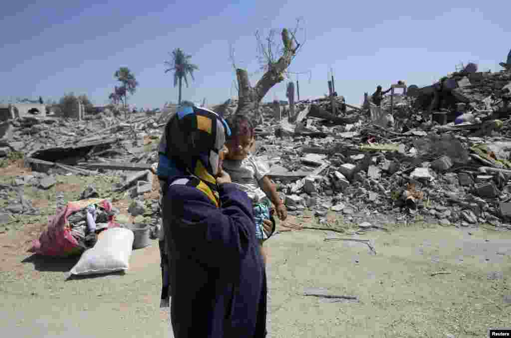 A Palestinian woman holds her daughter as they walk past the ruins of destroyed houses in Khuzaa town, which witnesses say was heavily hit by Israeli shelling and air strikes during the Israeli offensive, in the east of Khan Younis, in the southern Gaza Strip, Aug. 7, 2014.
