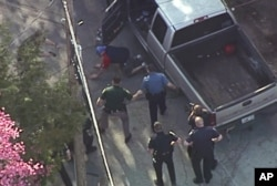 This aerial image made from a helicopter video provided by WHDH shows Richard Simone kneeling and putting his hands on the ground after a high-speed police pursuit in Nashua, New Hampshire, May 11, 2016.