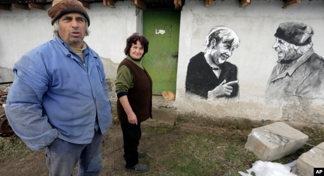 Ivanka and Krustyo Tonev pose next to the mural depicting German chancellor Angela Merkel, in the Bulgarian village of Staro Zhelezare, Jan. 27, 2016.