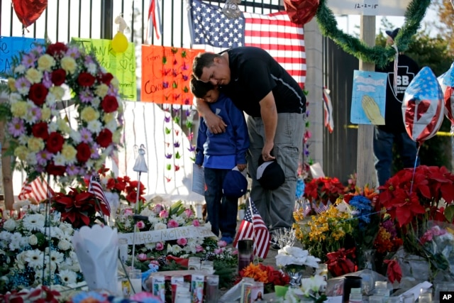 FILE - Gary Mendoza, and his son Michael pay their respects at a makeshift memorial site honoring shooting victims, in San Bernardino, Calif., Dec. 7, 2015.