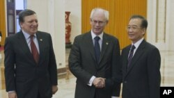 Chinese Premier Wen Jiabao, right, shakes hand with EU President Herman Van Rompuy beside European Commission President Jose Manuel Barroso before their meeting at the Great Hall of the People in Beijing , Feb. 14, 2012.