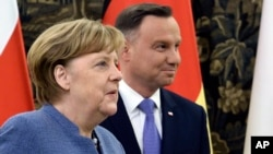 German Chancellor Angela Merkel, left, and Polish President Andrzej Duda walk for talks on European Union future and security and on bilateral ties, at the Belvedere Palace in Warsaw, Poland, March 19, 2018.