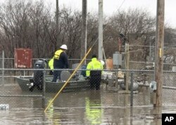 In this photo provided by the Missouri State Highway Patrol, Water Patrol troopers assist utility company employees in shutting off natural gas lines in floodwaters at Craig, Mo., March 20, 2019.