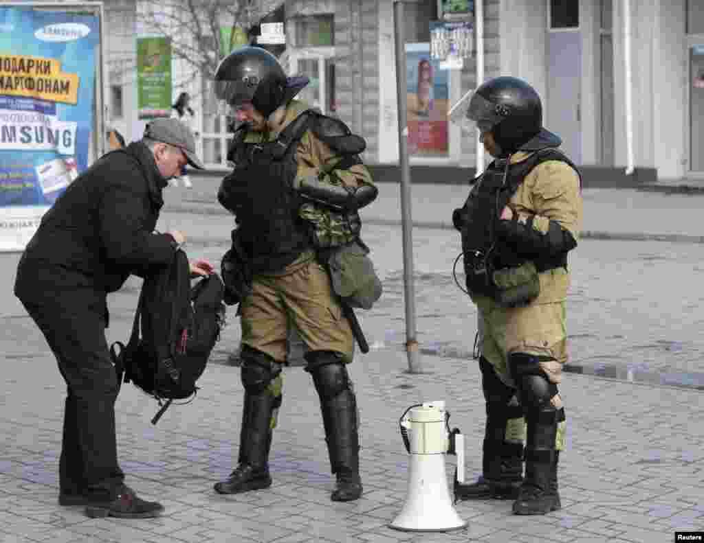 Các thành viên của đơn vị tự vệ Crimea kiểm tra túi xách của một người đàn ông trên đường phố Simferopol, ngày 17/3/2014.