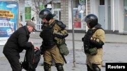 Members of a Crimean self-defense unit spot check a man's bag a street in Simferopol, Crimea, Ukraine, March 17, 2014.