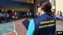 Un observateur de l'Union européenne regardent les citoyens faire la queue pour aller voter à Monrovia, le 10 octobre 2017.
