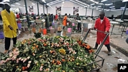 Workers push cart loaded with discarded fresh roses at a flower exporter's farm in Naivasha, 19 Apr 2010
