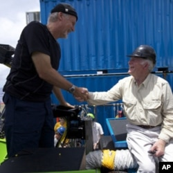 James Cameron is congratulated by U.S. Navy Capt. (Ret) Don Walsh, right, after completing the first ever solo dive down to the lowest part of the Mariana Trench, part of the Deepsea Challenge, a joint effort with National Geographic. Walsh took the same
