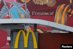 "The logo of McDonald's is seen in front of a house decorated with graffiti reading ""We are proud!"" and depicting the Order of Victory and a St. George's Ribbon, a symbol widely associated in Russia with the commemoration of victory in World War II, in central Moscow, Aug. 17, 2016."
