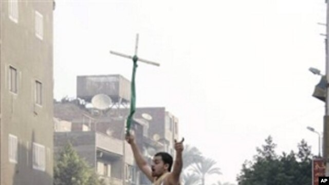 Angry Egyptian Christians smash a police vehicle as they raise a cross during a riot, which left one one person dead, after authorities halted construction on a church saying the local Christian community had violated a building permit, in Cairo, Egypt, W