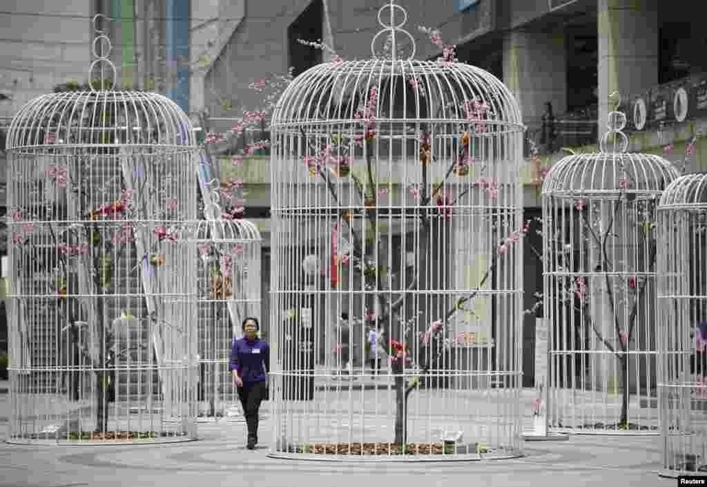 A woman walks past an installation of giant bird cages containing artificial trees and birds on a square in Nanjing, Jiangsu province, China.