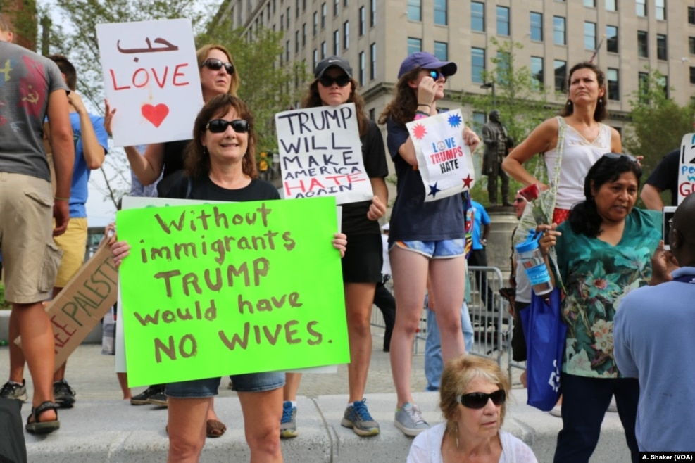"""反川普示威者拿着标语,把川普的竞选口号改了一个词,改成""""川普让美国再度仇恨""""。他们针对所谓的川普反移民立场,手持标语讽刺他说""""如果没有移民,川普就没有老婆了""""。川普的第一任和现任妻子分别来自捷克和斯洛文尼亚"""