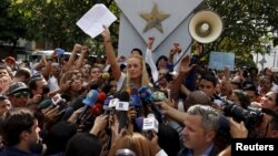 Lilian Tintori, wife of jailed Venezuelan opposition leader Leopoldo Lopez, holds up a letter from her husband as she speaks during a news conference in Caracas, Sept. 11, 2015.