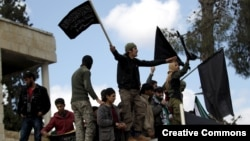 Protesters carry Jabhat al-Nusra flags and shout slogans during an anti-government protest after Friday prayers in the town of Marat Numan in Idlib province, Syria, March 11, 2016.