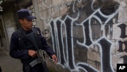 FILE - A member of the Salvadoran National Police walks next to symbol of the Mara Salvatrucha gang painted on a wall during an anti-gang operative in San Salvador, March 7, 2014.
