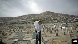 A girl, who sells water, closes her eyes as the wind blows her scarf at a cemetery in Kabul, Afghanistan, June 5, 2011
