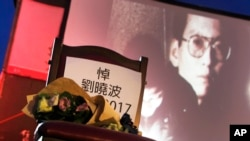 A bouquet of flowers is placed on a chair that reads ''Mourning Liu Xiaobo'' in front of his image during a ceremony to mourn late Nobel Peace Prize laureate Liu, China's most famous political prisoner, at Democracy Square in Taipei, Taiwan, July 14, 2017.