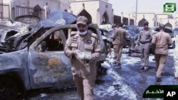 In this image from Saudi TV video, investigators collect evidence in the aftermath of a suicide bombing outside the Imam Hussein mosque in Dammam, Saudi Arabia, May 29, 2015.
