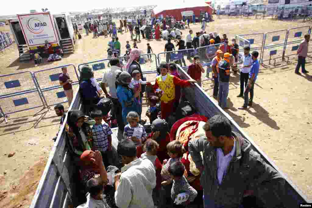 Kurdish Syrian refugees stand in a truck at the Turkish-Syrian border near the southeastern town of Suruc in Sanliurfa province, Sept. 25, 2014.