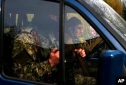一名欧安会观察员(右一,背景处)在乌克兰东部的斯拉维扬斯克工作,前景为武装亲俄分子驾驶的汽车从镜头前开过 。摄于2014年4月24日。