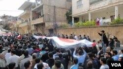 Demonstran anti pemerintah membawa bendera Suriah dalam protes di Zabadani, dekat Damascus (22/4).