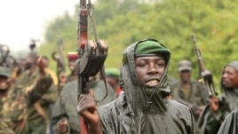 M23 rebel fighters celebrate in the rain at Rumangabo after government troops abandoned the town 23 kilometers north of the eastern Congolese city of Goma, July 28, 2012.