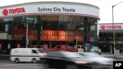 FILE - Vehicles speed past a Toyota dealership in Sydney.