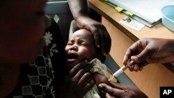 Majka drži dijete kako prima novo cjepivo protiv malarije u sklopu ispitivanja u istraživačkom centru Walter Reed Project u Kombewi u zapadnoj Keniji.