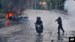 2018年5月28日,在尼加拉瓜馬納瓜舉行的抗議尼加拉瓜總統丹尼爾奧爾特加活動期間,一名警察用霰彈槍瞄準兩名駕駛電單車的男子。