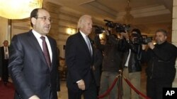 Iraq's Prime Minister Nouri al-Maliki (L) walks with U.S. Vice President Joe Biden, center, after his arrival for a meeting in Baghdad, Iraq, 13 Jan 2011