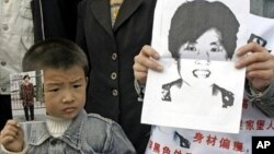 A young boy holds up a photo of his mother as he joins family members wearing posters describing the woman as missing from her home in Xian, northern China's Shaanxi province, as they launch a campaign to locate her (File Photo).