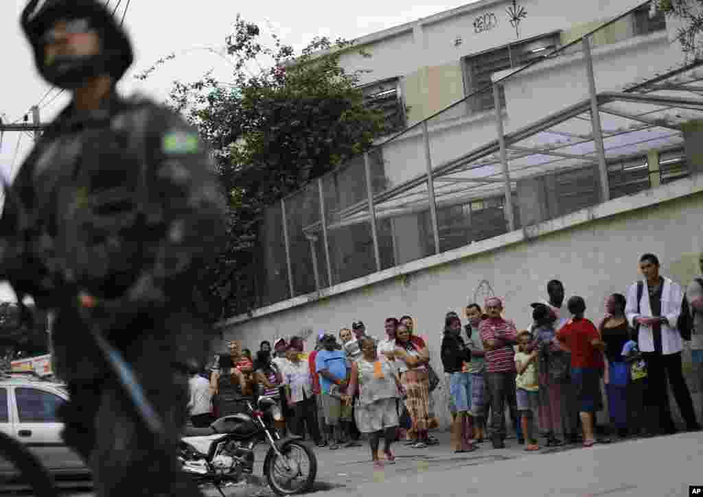 A soldier stands guard where people wait in line to vote in general elections outside a school at the Mare Complex slum in Rio de Janeiro, Brazil, Oct. 26, 2014.