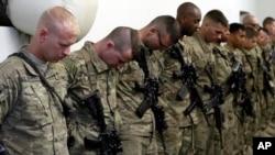 在阿富汗库纳尔省,美国陆军第35步兵师第二营第二连的军人在结束驻阿使命的仪式上低头默哀,悼念死去的战友。(资料照)