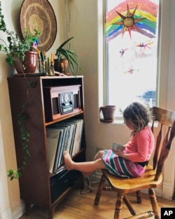 In this April 2, 2020, photo provided by Cassy Quinlan, 4-year-old Polly Fraley listens in Homer, Alaska, to children's stories being read on air at local radio station KBBI by librarian Claudia Haines.