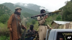FILE - Pakistani Taliban patrol in their stronghold of Shawal in Pakistani tribal region of South Waziristan.