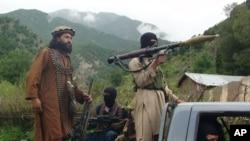 FILE - Pakistani Taliban patrol in their stronghold of Shawal in Pakistani tribal region of South Waziristan.