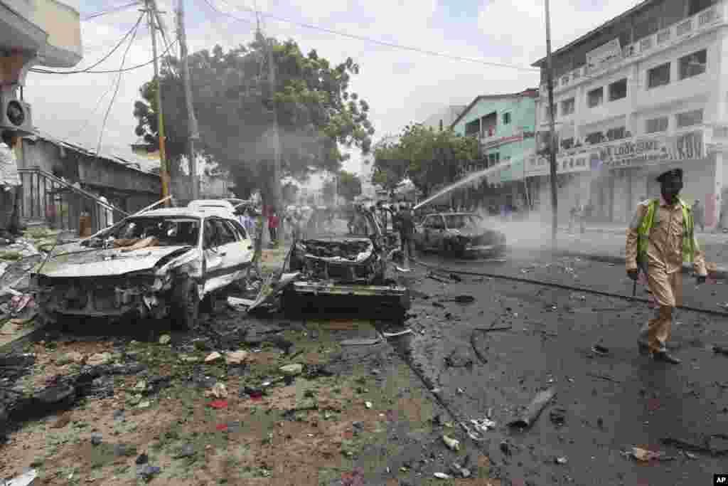 Un soldat somalien patrouille près des voitures détruites après l'attentat près d'un centre commercial à Mogadiscio, en Somalie, le 30 juillet 2017.