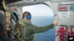 In this photo released on Aug. 7, 2015 by the French Army Communications Audiovisual office (ECPAD), a crew member looks out of the airplane door taking part in the search for wreckage from the missing MH370 plane off the coasts of the French island of La Reunion.