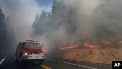 一辆消防车驶过熊熊燃烧的加州野火。(2013年8月26日)