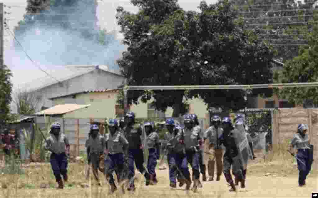 Police leavethe scene after throwing teargas at a house in Chitungwiza, Zimbabwe, Sunday, Nov. 6, 2011. The party of Zimbabwe's prime minister says 22 people were injured and property was destroyed after ruling party militant youths attacked hundreds of s