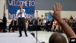 President Barack Obama takes a question from a man in the audience at Taylor Stratton Elementary School in Nashville, Tenn., where he spoke about the Affordable Care Act, July 1, 2015.