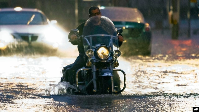A man on a motorcycle drives through flood water on Western Ave. at NW 5th Street in Oklahoma City on Friday, May 31, 2013.