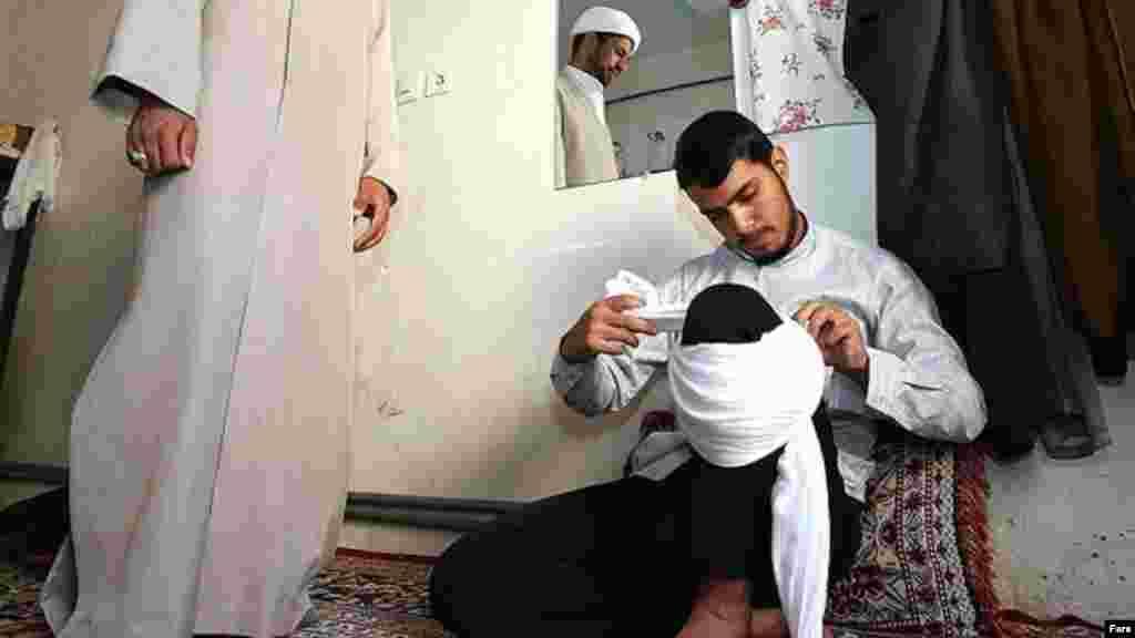 یک جوان در مراسم عمامه گذاری مدرسه علمیه امام صادق در تایباد خراسان، تمرین می کند چطور عمامه خود را ببندد. عکس: محمدجواد مشهدی، فارس