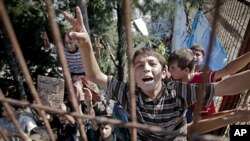 Syrian refugee children shout during a spontaneous protest they initiate against Syrian President Bashar al-Assad, in a camp in Yayladagi, Turkey, near the Syrian border, June 15, 2011