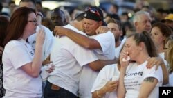 Friends and family grieve during a vigil to honor Pulse night club victim Corey Connell at Publix in College Park, Fla., on Thursday, June 16, 2016. (Stephen M. Dowell (Orlando Sentinel via AP)