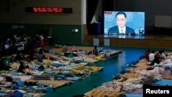 한국 전남 진도군 실내체육관에 머물고 있는 세월호 침몰 사고 실종자 가족들이 27일 정홍원 총리의 사의 표명 긴급 기자회견 중계를 바라보고 있다.