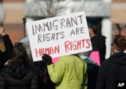 FILE - A supporter holds up a placard during a rally outside the Immigration and Customs Enforcement office in Centennial, Colorado, Feb. 15, 2017.