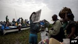Des personnes embarquent dans des pirogues sur le lac Albert pour fuir les violences en Ituri vers l'Ouganda à Tchomia, le 5 mars 2018.